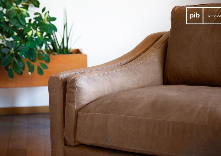 Deze 3-zitsbank met zijn rijkelijk gevoerde zitkussens boven de gekruiste riemen biedt een