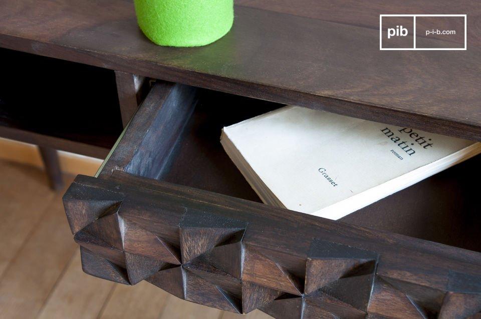 De combinatie van donkere houten poten een lade met geometrische reliëfs geven de Balis houten