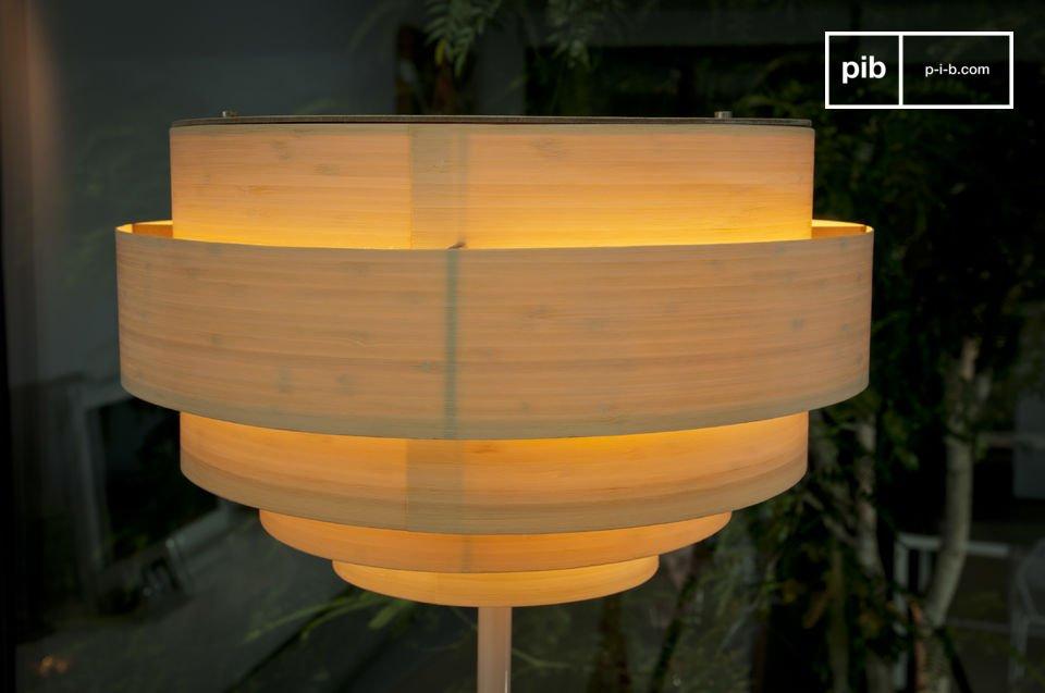 De Boréals lampenkap is bevestigd op een witte metalen lampenvoet die ervoor zorgt dat er mooi warm