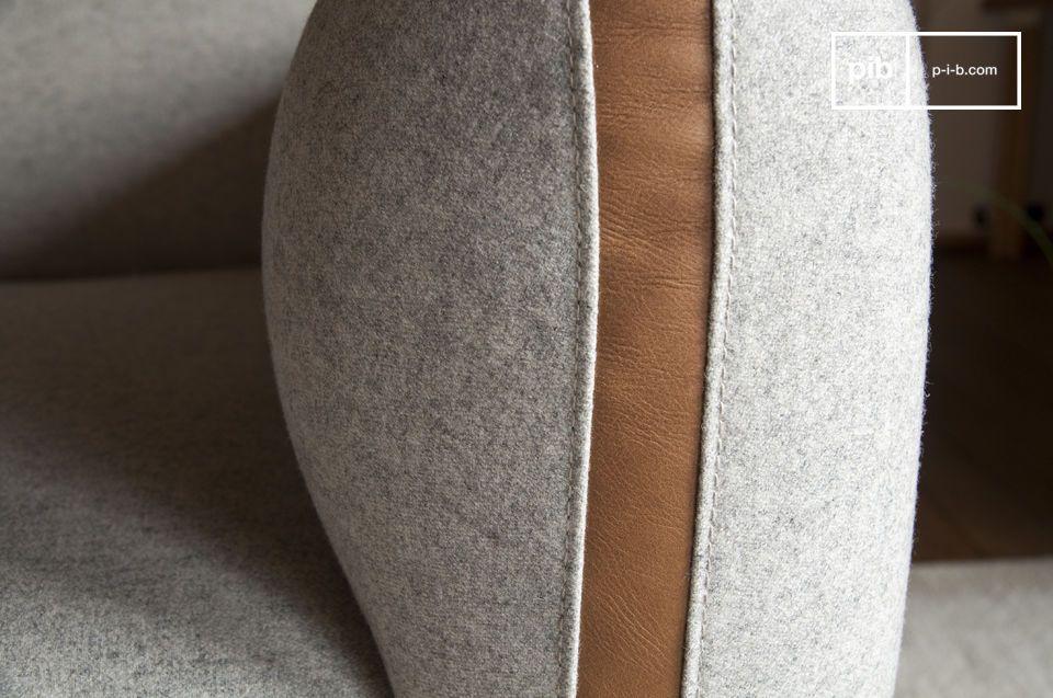 Deze lichtgrijze fauteuil neemt een \'60\'s\' look uit met zijn leren bekleding