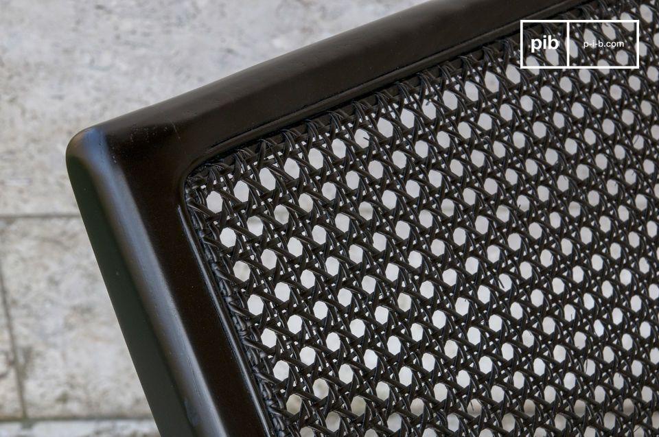 Met zijn eenvoudige lijnen en intens zwarte kleur brengt deze rieten stoel een vleugje elegantie en