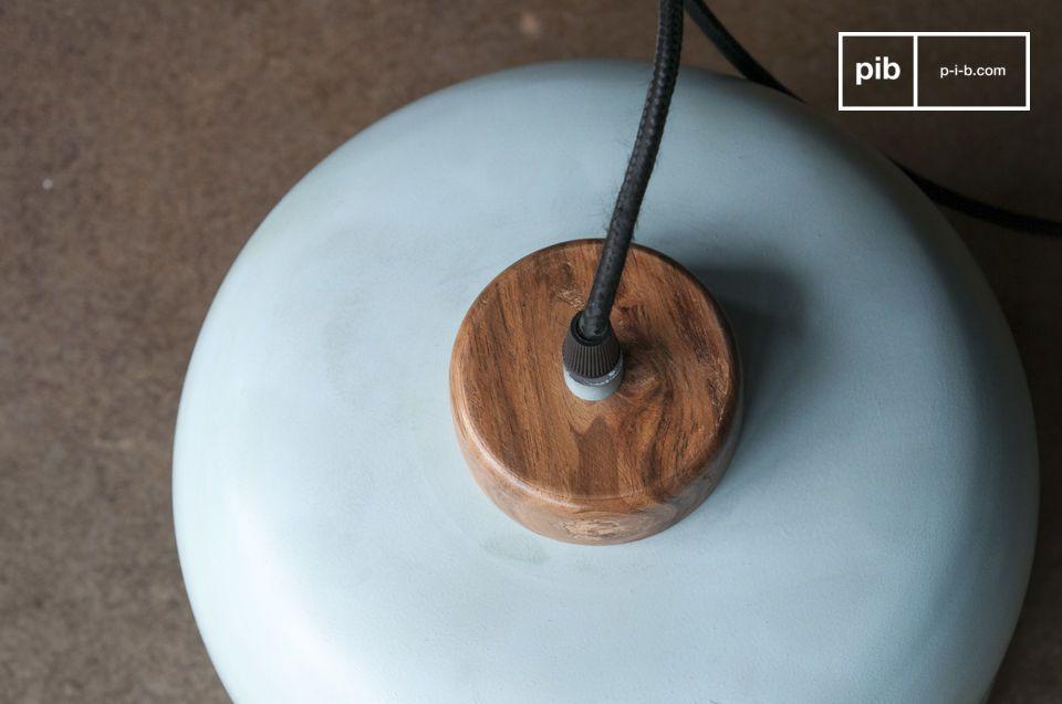 De gelakte steun van ruw hout contrasteert met de finesse van de lichte turquoise metalen kap om