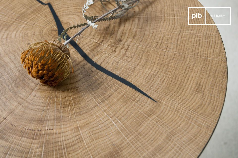 De natuurlijke scheur in het stuk hout is gevuld met zwart en doet denken aan de kleur van de voet