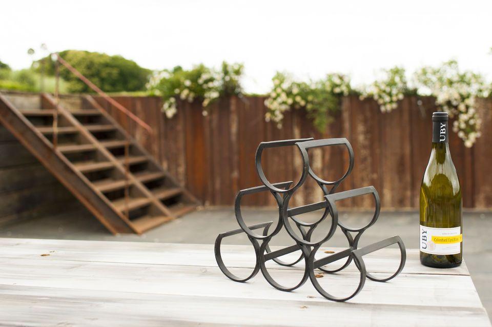 Een piramidevormig metalen rek met 6 ronde opslagplaatsen om 6 flessen wijn of sterke drank te