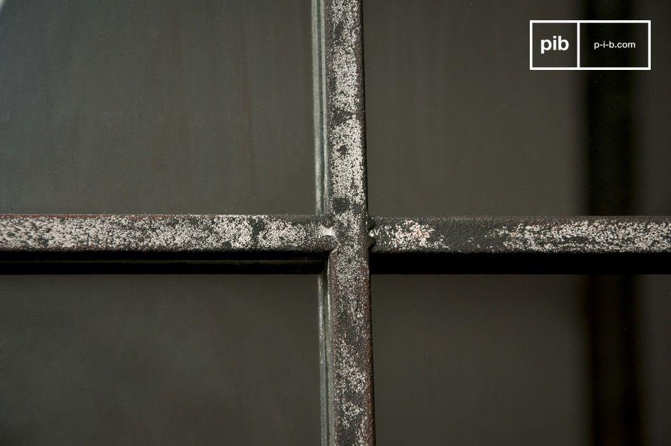De metalen frame van de spiegel heeft gebruikssporen en is geïnspireerd op de oude ramen van