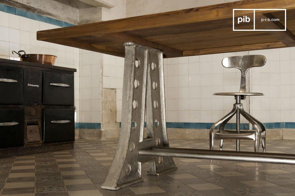 De tafel heeft stalen poten in een Eiffeltoren stijl en een dikke stevige tafelblad van teakhout