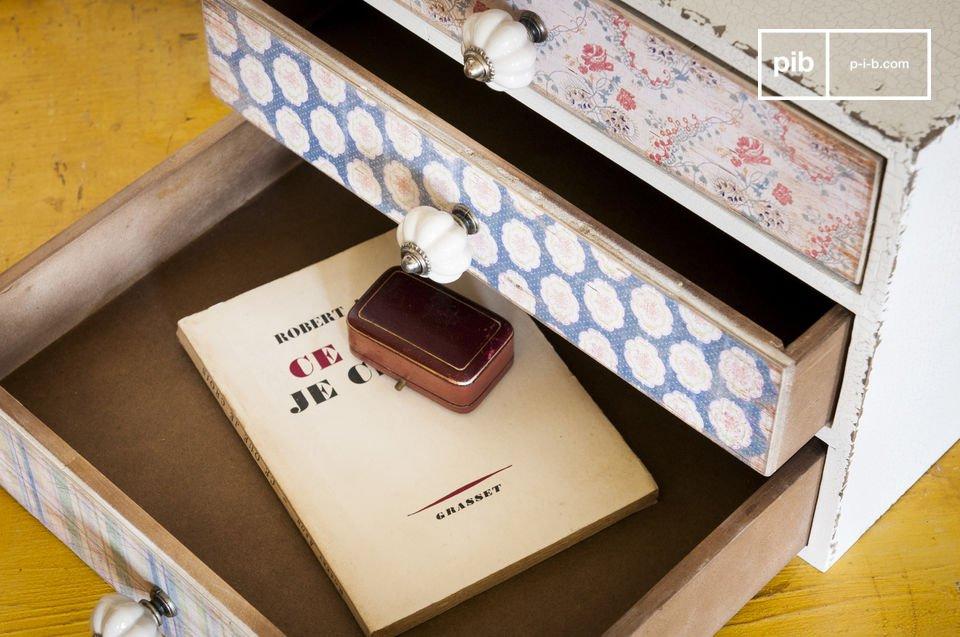Dit kleine meubelstuk heeft drie verschillende lades, elke voorzien van een ander bloemenmotief